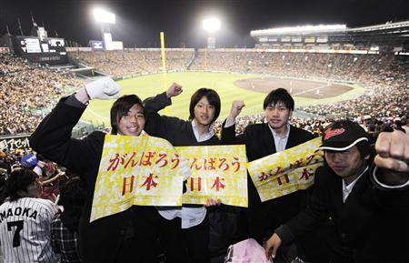プロ野球が開幕した甲子園球場で被災者を応援するメッセージを掲げる、阪神大震災の年に生まれた地元の高校生=12日夜、兵庫県西宮市
