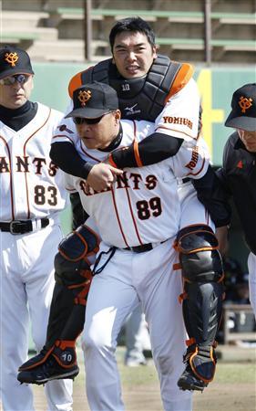 阪神との練習試合で右ふくらはぎを痛め、村田コーチに背負われ交代する阿部捕手=相模原(2011年4月5日、共同)