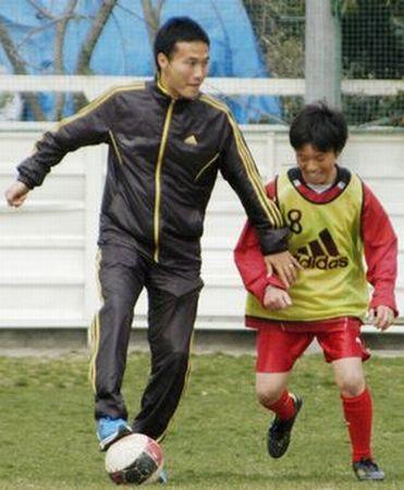 宮城県亘理町を訪れ、子どもとサッカーをする日本代表の今野泰幸選手(2011年4月11日、共同)