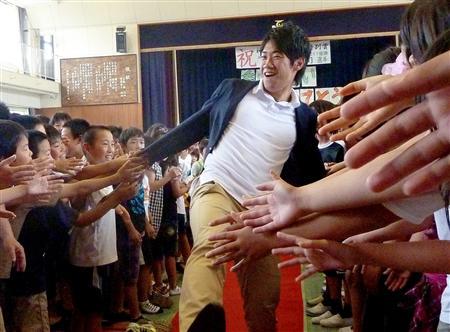 神戸市の母校の小学校で後輩たちから歓迎の握手攻めにあう香川真司選手(2011年6月22日、共同))