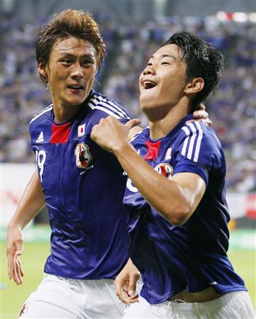 日本―韓国戦で、先制ゴールを決め喜ぶ香川(右)と祝福する李=10日、札幌ドーム