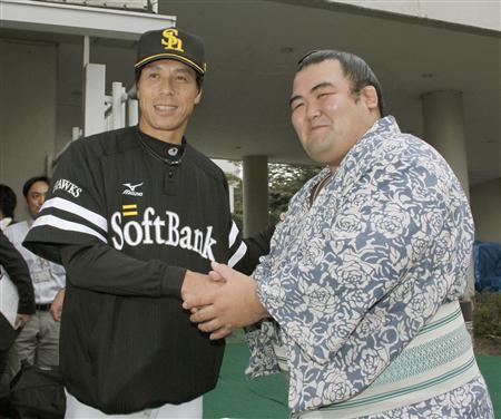 ほやほやの新大関琴奨菊は、パ・リーグ2連覇を決めたばかりのソフトバンク秋山監督と祝福の握手を交わした(2011年10月2日、西武ドームで。共同)
