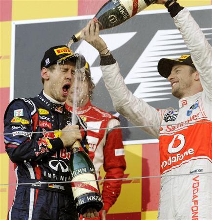 日本GPの表彰式でバトン(右)に祝福されるフェテル