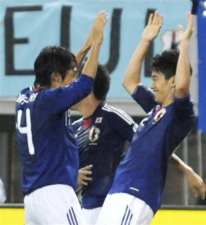 日本―タジキスタン 前半、4点目のゴールを決め、アシストした中村(左)とハイタッチする香川=長居
