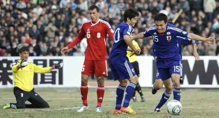 アウェーのタジキスタン戦で今野(15)が先制ゴールを決めて駆けだす。隣は香川(2011年11月11日、ドゥシャンベ、共同)