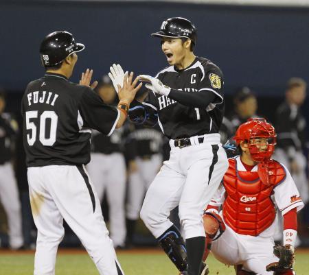 8回に勝ち越し2ランを放ち藤井彰(左)に迎えられる鳥谷。珍しく表情に生気がみなぎる。(5月8日、共同)