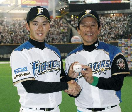 西武との今季開幕戦に快勝。ウイニングボールを手に満面に笑みの栗山新監督(右)とプロ初の完投勝利を挙げた斎藤(3月30日、札幌ドーム、共同)