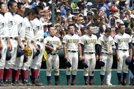 大阪桐蔭(手前)に敗れてベンチ前に整列する光星学院ナイン。またも決勝戦の後、自分たちの校歌を歌う栄誉を逃した。(8月23日、共同)