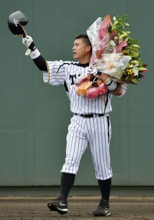 引退試合となったウエスタン・リーグのオリックス戦で、花束を手にファンの声援に応える阪神・城島=9月29日、鳴尾浜(共同)