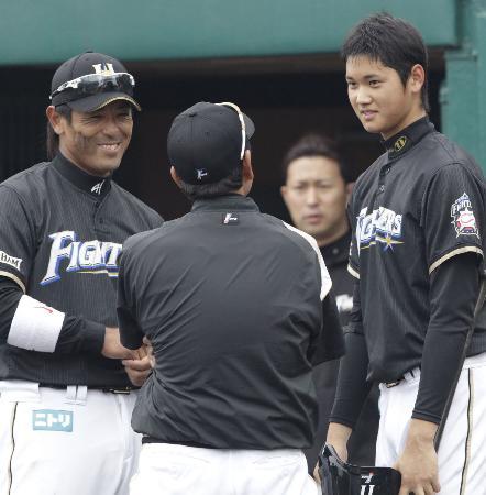 打撃練習後に栗山監督(背中)稲葉コーチ兼内野手(左)からアドバイスを受ける大谷(2013年2月13日、名護、共同)