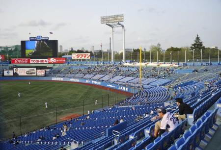 神宮球場の一塁側スタンドから見たスコアボード(左)など外野席の景観。グラウンドでは試合開始前の練習が行われている(共同)