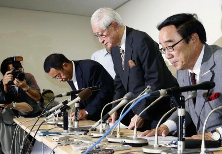 記者会見を終え引き揚げる日本野球機構の加藤良三コミッショナー(右から2人目)ら=14日午後、東京・内幸町のNPB事務局