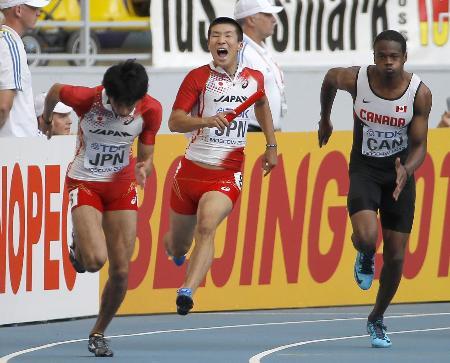 男子400メートル決勝で第2走者の藤光(左)にバトンを渡す桐生。その形相と宙を駆けるような走りが印象的(2013年8月19日、共同)