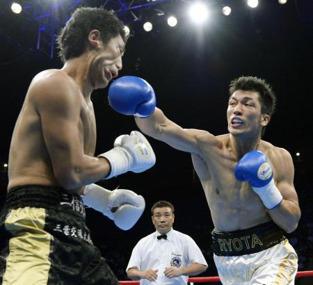 プロデビュー戦で圧勝した村田諒太(右)。五輪金メダリストの重く鋭いパンチに東洋太平洋ミドル級王者の柴田明雄の顔は大きく歪んだ(2013年8月25日、共同)