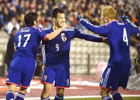 3点目のゴールを決め、長谷部(左)、本田(右)と喜ぶ岡崎=ブリュッセル(共同)