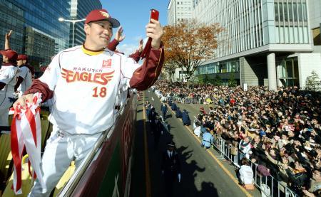 優勝パレードのバスに乗り込み、沿道のファンを携帯電話のカメラで撮影する楽天・田中