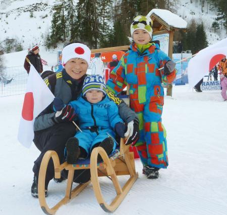 W杯を転戦する日本選手たちに手作りの和食を差し入れし、応援にも精を出す距離スキー元五輪代表の横山久美子さん(左)と次男志文(中央)長男の健志君(2013年12月15日、ラムソー、共同)