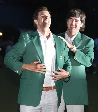暗闇の中で行われた表彰式でグリーンジャケットに袖を通し、感無量の面持ちのアダム・スコット。右は前年優勝のバッバ・ワトソン(2013年4月15日、共同)