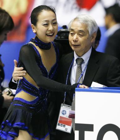女子フリーの演技を終えた浅田真央(左)を迎える佐藤信夫コーチ。昨年11月のNHK杯から(2013年11月9日、共同)