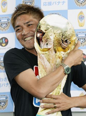 サッカーW杯日本代表に選ばれ、報道陣が用意した手作りのW杯トロフィーを手に笑顔の大久保嘉人=12日午後、羽田空港