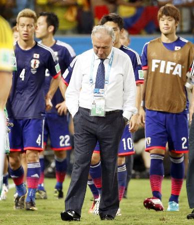 コロンビアに敗れて1次リーグ敗退が決定し、打ちひしがれて引き揚げるザッケローニ監督。左は本田(2014年6月24日、共同)