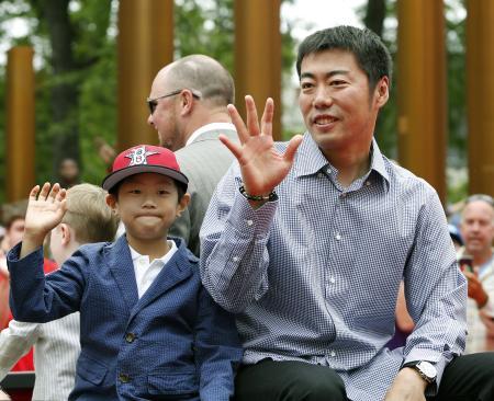 米大リーグオールスター戦恒例の街頭パレードに参加、ファンに手を振るレッドソックスの上原投手と長男の一真君。父子にとっても得がたい思い出となった。(2014年7月15日、共同)