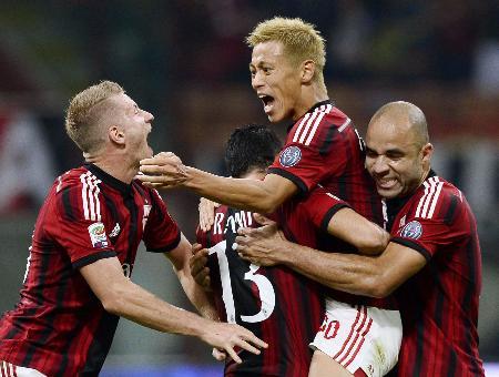 キエボ戦の後半、今季4点目のゴールを決め、祝福されるACミランの本田(右から2人目)=ミラノ(共同)