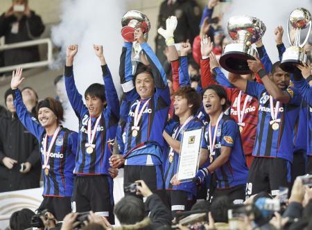 天皇杯を制して国内主要タイトル3冠を達成、トロフィーを掲げる遠藤(左から3人目)、パトリック(右端)らG大阪イレブン