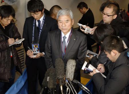 報道陣に囲まれ八百長疑惑の質問に重い口を開く日本サッカー協会の大仁邦弥会長(中央)(2014年12月18日、共同)