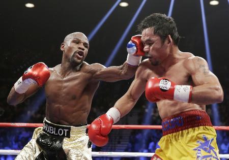 ボクシングの世界ウエルター級王座統一戦で、マニー・パッキャオ(右)の顔面にパンチを浴びせるフロイド・メイウェザー=2日、ラスベガス(AP=共同)