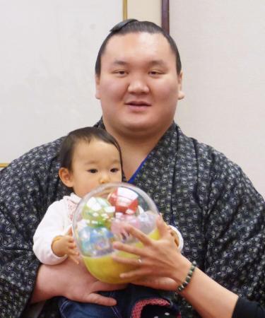 日本相撲協会のファンサービス企画で赤ちゃんを抱っこする横綱白鵬(2014年12月25日、共同)