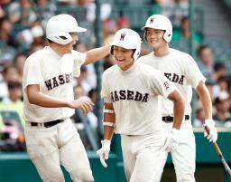 早実―九州国際大付 4回裏、2打席連続となる2点本塁打を放ち、ナインに迎えられる早実・富田(中央)=甲子園