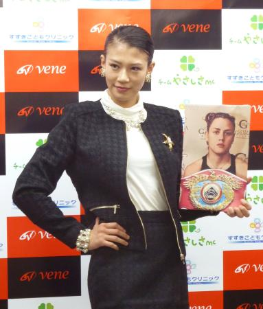対戦が決まり、WBO女子スーパーフライ級王者ダニエラ・ベルムデスの写真を手にポーズをとる高野人母美=7日、東京都新宿区の協栄ジム