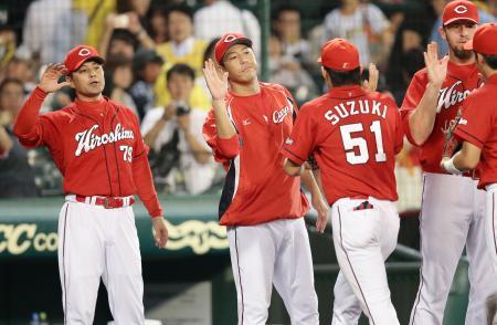 阪神に勝利し、ナインを迎える広島の(左から)緒方監督と黒田=甲子園