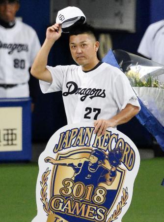 7月28日の阪神戦に先発し、3018試合のプロ野球最多出場記録を達成。記念ボードを掲げる中日・谷繁=ナゴヤドーム