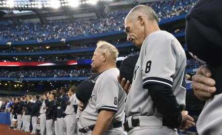 ブルージェイズ戦前にヨギ・ベラ氏の背番号「8」をユニホームの左袖に付けて黙とうするヤンキースのジラルディ監督(右端)ら=トロント(共同)