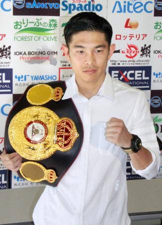初防衛から一夜明け、チャンピオンベルトを肩に掛けポーズを取るWBAフライ級王者の井岡一翔=28日、大阪市の井岡ジム