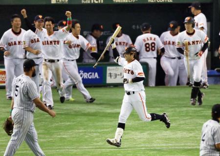 10回、サヨナラの押し出し四球を選び、バットを掲げ一塁へ向かう巨人の代打高橋由=東京ドーム