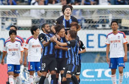 G大阪―新潟 後半、FKを決めイレブンに祝福されるG大阪・遠藤(中央下)=万博