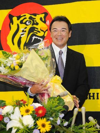 退任記者会見を終え、花束を手に笑顔の阪神・和田監督=13日、大阪市の阪神電鉄本社