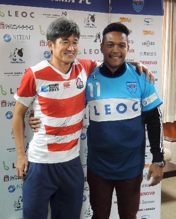 ユニホームを交換し、ポーズをとるJ2横浜FCの三浦(左)とラグビー日本代表の松島=18日、ニッパツ三ツ沢球技場