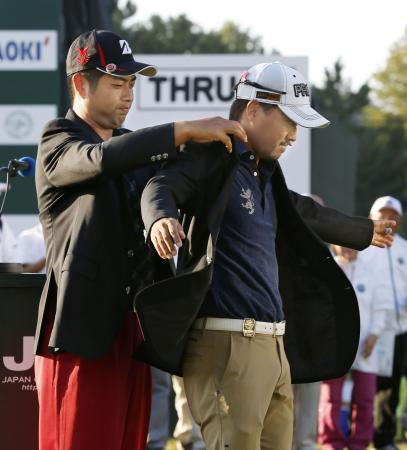 日本オープンで初優勝を果たし、前回覇者の池田雄太(左)からチャンピオンブレザーを着せてもらう小平智。2人のデッドヒートは見ごたえがあったが、松山英樹、石川遼の不在にアダム・スコットは残念そうな感想を口にした(2015年10月18日、共同)