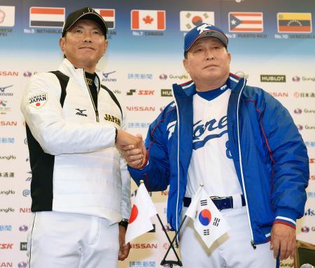 記者会見を終え、握手する日本代表の小久保監督(左)と韓国代表の金寅植監督=7日、札幌市内のホテル