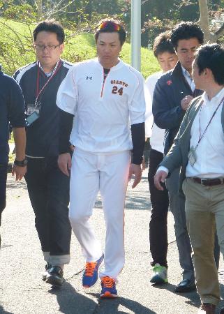 報道陣とともに球場に向かう、プロ野球巨人の高橋監督=10日午前、宮崎市