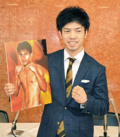 初防衛戦の対戦相手の写真を手にポーズをとる田中恒成=10日、名古屋市