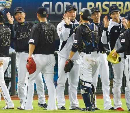 ドミニカ共和国に競り勝ち、中田(13)ら日本代表ナインとタッチを交わす小久保監督(左端)=桃園(共同)