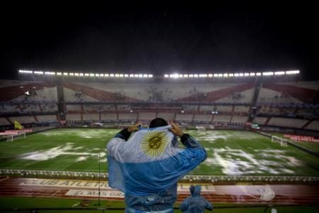 スタンドで国旗をかぶり、豪雨を避けるアルゼンチンのサポーター=12日、ブエノスアイレス(AP=共同)