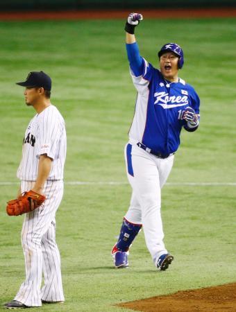 日本戦の9回、逆転2点打を放ちガッツポーズする韓国の李大浩。左は中田=東京ドーム