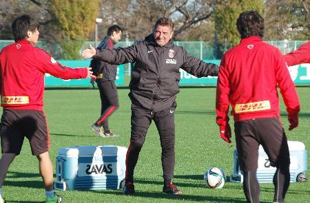 練習中、選手とタッチする浦和のペトロビッチ監督(中央)=さいたま市