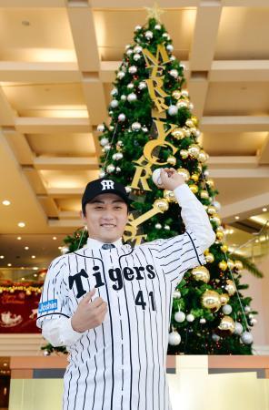 入団記者会見場のホテルに飾られたクリスマスツリーの前で、ポーズをとる阪神の高橋聡文投手=1日、兵庫県西宮市
